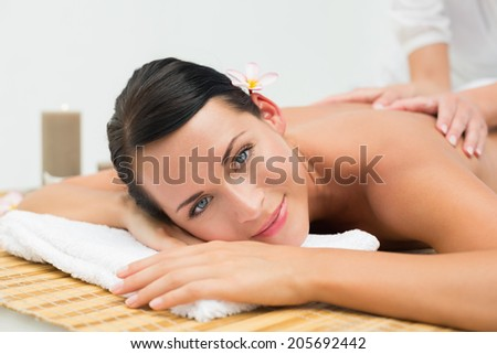 Peaceful brunette enjoying a back massage smiling at camera in the health spa - stock photo