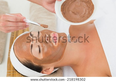Peaceful brunette getting a mud treatment facial in the health spa - stock photo