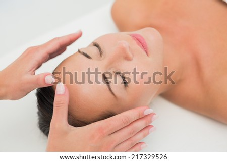 Peaceful brunette getting reiki therapy in the health spa - stock photo