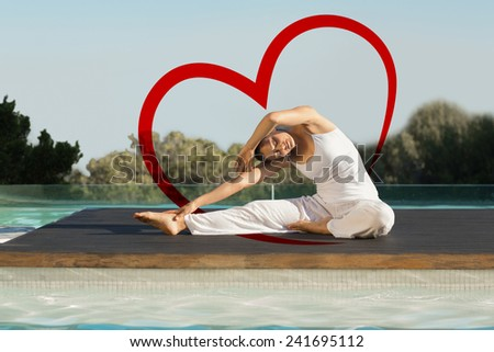 Peaceful brunette in janu sirsasana yoga pose poolside against heart - stock photo