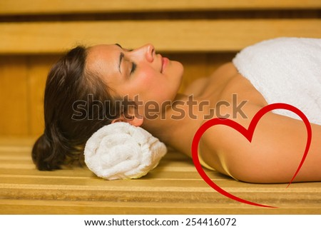 Peaceful brunette relaxing in a sauna against heart - stock photo
