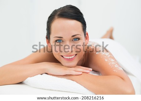 Peaceful brunette smiling at camera with salt scrub on back in the health spa - stock photo