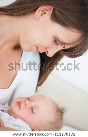 Peaceful brunette woman holding her little daughter indoors - stock photo