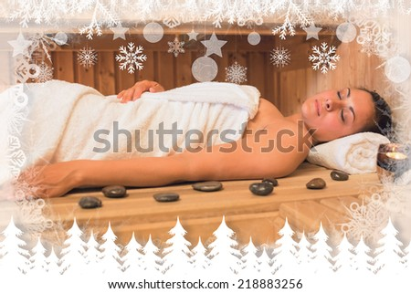 Peaceful brunette woman lying in a sauna against fir tree forest and snowflakes - stock photo