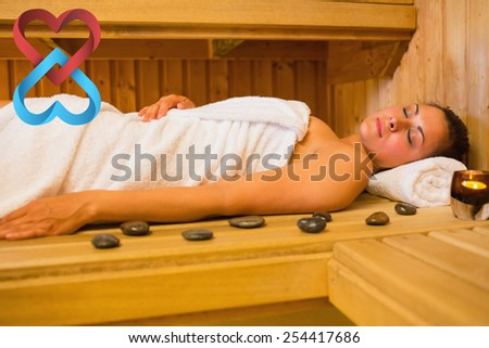 Peaceful brunette woman lying in a sauna against linking hearts - stock photo