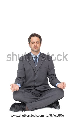 Peaceful businessman meditating in lotus pose on white background
