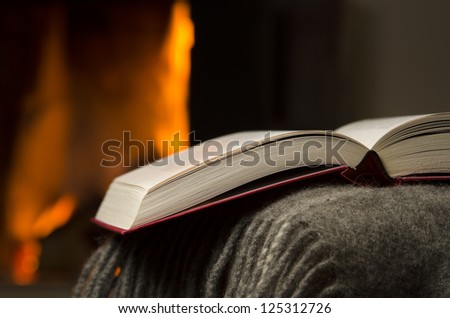 Peaceful closeup of open book resting on a arm rest of a couch. Warm fireplace on background. - stock photo