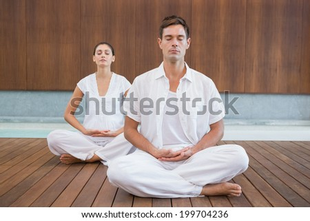 Peaceful couple in white sitting in lotus pose together in health spa - stock photo