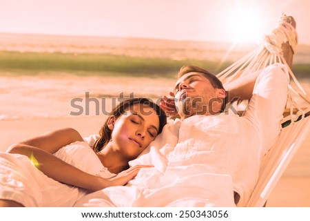 Peaceful couple napping in a hammock at the beach - stock photo