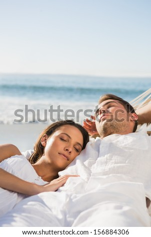 Peaceful couple sleeping in a hammock on the beach - stock photo