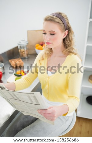 Peaceful cute blonde reading newspaper in bright kitchen