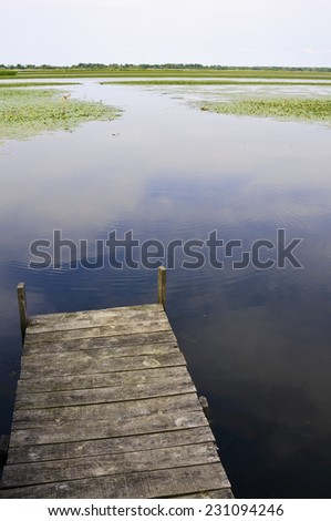 Peaceful jetty at lakeside with sky reflection on water - stock photo
