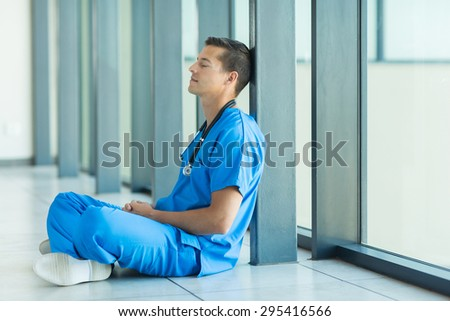 peaceful male doctor relaxing on hospital floor - stock photo