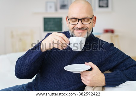 Peaceful mature bearded and bald handsome male with eyes closed while holding cup of coffee near his face and seated - stock photo