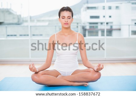 Peaceful natural brown haired woman in white sportswear practicing yoga in bright living room - stock photo