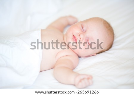 Peaceful newborn baby lying on a bed sleeping on white sheets