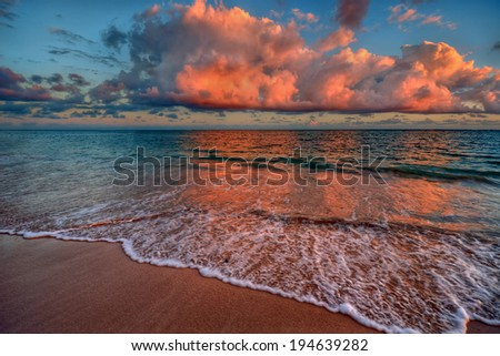 Peaceful ocean sunset with crimson clouds and sandy beach - stock photo
