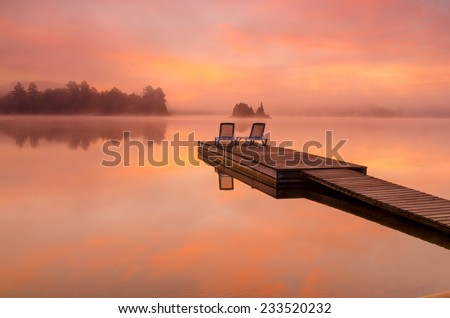 Peaceful scene by the lake on a beautiful foggy morning - stock photo