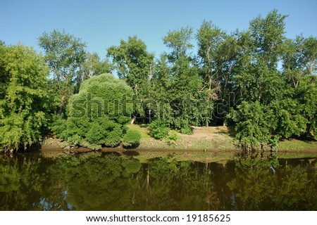 Peaceful scenic view of river and landscape in summer morning