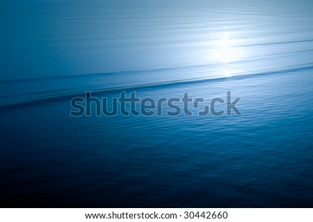 peaceful sea water surface with sunlight reflection - stock photo