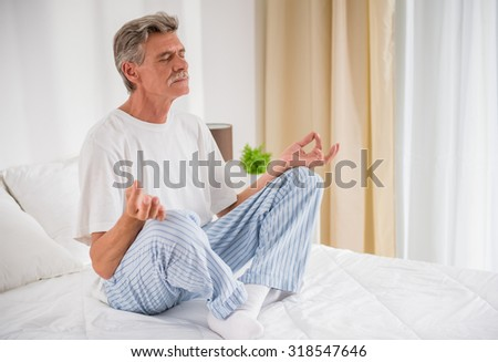 Peaceful senior man meditating seated on a bed. - stock photo