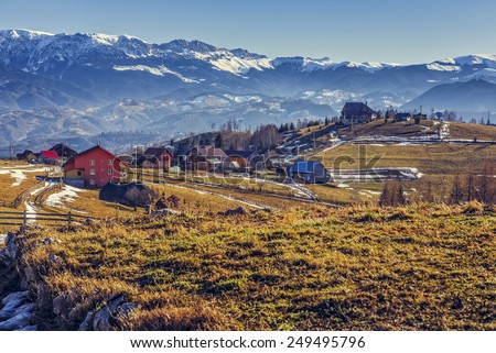 Peaceful sunny rural landscape with hamlet and grasslands in Pestera village, Brasov county, Romania. Bucegi mountains range on the horizon. - stock photo