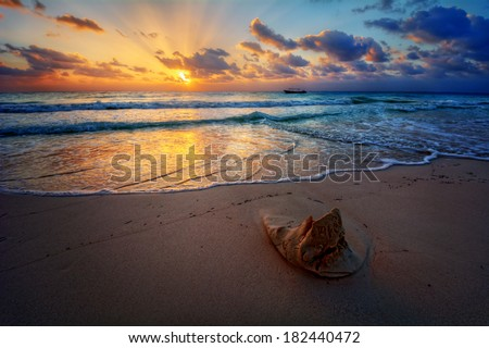 Peaceful sunrise with god rays over pristine sandy beach with a sand sculpture in the foreground - stock photo