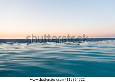 peaceful sunset at sea in soft, pastel colors - stock photo