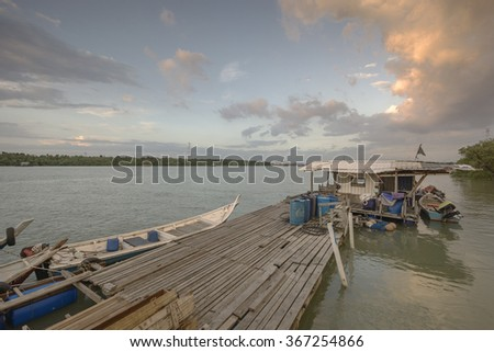 Peaceful sunset with dramatic sky with boats and jetty