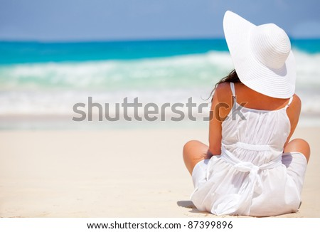 Peaceful woman at the beach contemplating the ocean and relaxing - stock photo