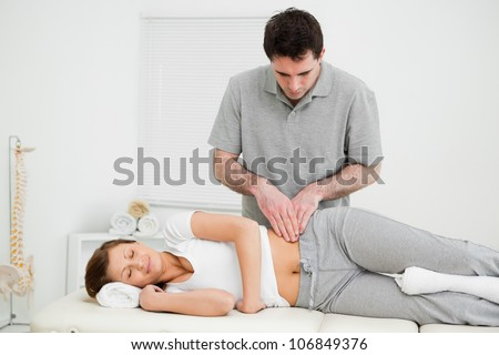 Peaceful woman being massaged on her hip by a doctor in a medical room