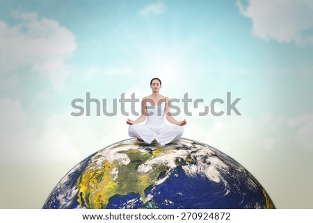 Peaceful woman in white sitting in lotus pose against blue sky - stock photo