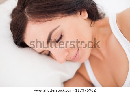 Peaceful woman lying while sleeping in her bedroom