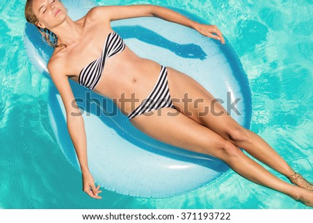 Peaceful woman on lilo in the pool