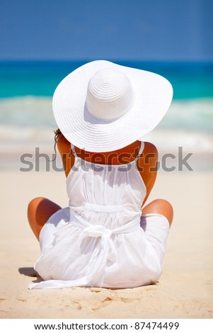Peaceful woman sitting at the beach  enjoying the view - stock photo