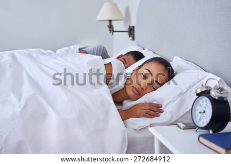 peaceful young couple sleeping comfortably in bed at home - stock photo