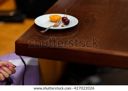 Peach and cherry lie on a white plate standing on the wooden table - stock photo