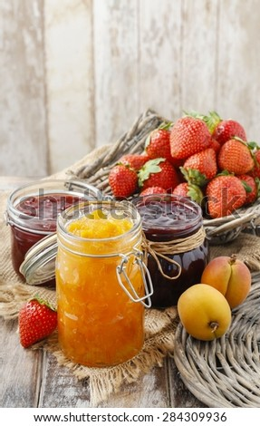 Peach, blueberry and strawberry jams in glass jars - stock photo