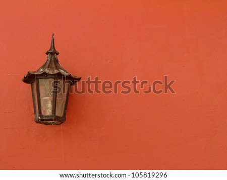 Peach colored colonial wall with old street lamp on an old architectural restored building in old san juan puerto rico - stock photo