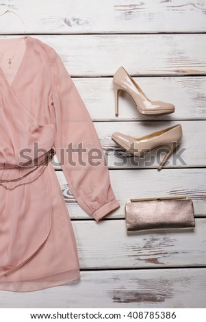Peach dress and clutch bag. Shelf with dress and purse. Girl's luxury accessory and clothing. Trendy outfit in boutique. - stock photo