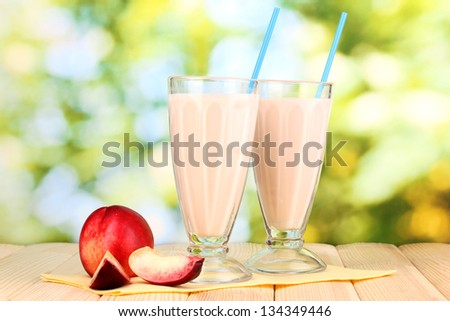 Peach milk shakes on wooden table on bright background - stock photo