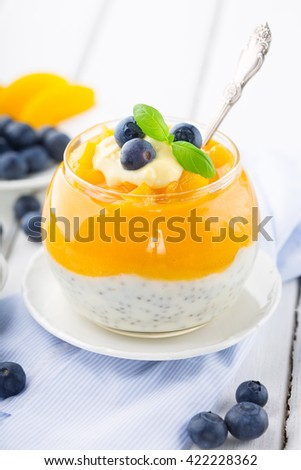 Peach smoothie with fresh tropical fruits, chia seeds and blueberries in jar for breakfast on white rustic wooden background, selective focus