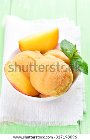 Peach sorbet decorated with mint in white bowl - stock photo