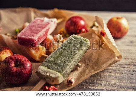 peach, strawberry and pistachio yellow, orange, red and green ice cream on wooden table