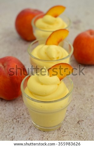 Peach swirl dessert mousse in small glasses garnish with slices of peach