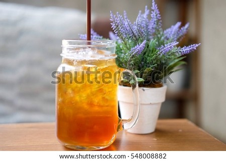 Peach Tea in jar on the table wood decorated with small flowerpot behind.
