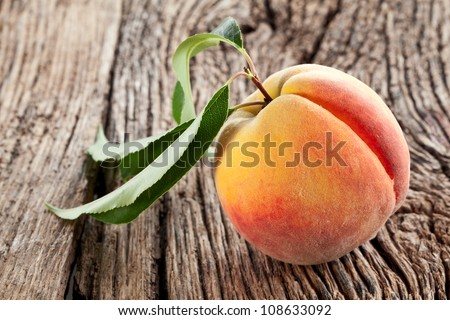 Peach with leaves on the old wooden table. - stock photo