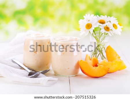 peach yogurt with fresh fruits on wooden table - stock photo