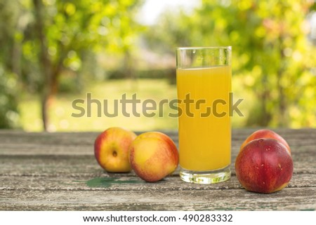 peaches and peach juice on a wooden table, outdoor