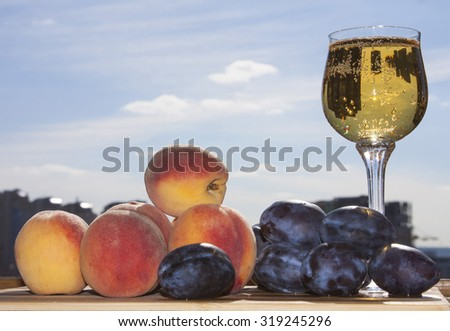 Peaches and plums with wine. Sunny day. - stock photo